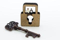 Миниатюрные люди: Бизнесмены сидя на ключе для всех замков и читая газету Отображайте польза для незаменимого работника, ключ к у Стоковые Изображения RF