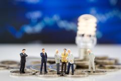 Миниатюрные люди, бизнесмены стоя на монетках, думая решение для дела, свет группы лампы идея Стоковое Фото