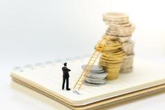 Миниатюрные люди: Бизнесмен думая и стоя на стоге монеток с лестницей Отображайте польза для роста денежной массы вверх, концепци стоковая фотография rf