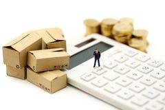 Миниатюрные люди: Бизнесмен и коробка с монетками и Calculat стоковая фотография rf