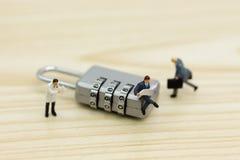 Миниатюрные люди: Бизнесмен сидя на зашифровании ключа для всех замков Отображайте польза для системы безопасности предпосылки, м Стоковые Изображения