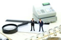 Миниатюрные люди: бизнесмен стоя на калькуляторе используя как ба Стоковое фото RF
