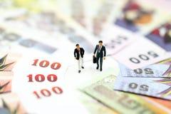 Миниатюрные люди: Бизнесмен стоя с деньгами, финансовый жулик стоковое изображение rf