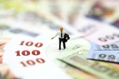 Миниатюрные люди: Бизнесмен стоя с деньгами, финансовый жулик стоковые изображения