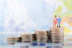 Миниатюрные люди, взрослые пары вычисляют положение na górze монеток стога Отображайте польза для планирования выхода на пенсию п Стоковые Фотографии RF