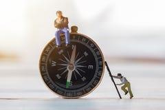 Миниатюрные люди вычисляют бизнесмена, сидят на компасе a Стоковое Изображение