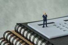 Миниатюрные люди вычисляют бизнесмена стоя на белом калькуляторе Стоковое Изображение RF
