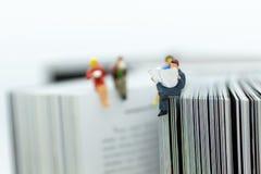 Миниатюрные люди: газета чтения бизнесмена на большой книге Отображайте польза для образования предпосылки или концепции дела стоковые изображения
