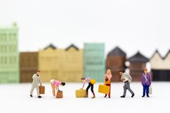 Миниатюрные люди: Люди группы носят чемодан сумки Польза изображения для концепции дела стоковое фото rf