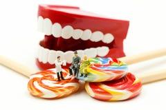 Миниатюрные люди: Дантист рассматривая зубы пациента с пациентом и сладкими леденцами на палочке, концепцией здравоохранения меди стоковые изображения