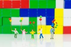 Миниатюрные люди: Дети держа фронт воздушного шара цвета деревянного блока Отображайте польза на день предпосылки международный с Стоковая Фотография RF