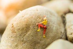 Миниатюрные люди: Женщины играют спорт максимума взбираясь Использованный как предпосылка для концепции дела перемещения приключе Стоковое Изображение RF