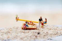 Миниатюрные люди: Игра детей на качаниях на пляже с стоковое фото rf