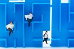 Миниатюрные люди: Книги чтения бизнесмена на лабиринте Отображайте польза для находить решение для разрешите проблему, концепцию  Стоковое Фото