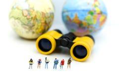 Миниатюрные люди: Команда путешественника с биноклями и картой мира b Стоковые Фотографии RF