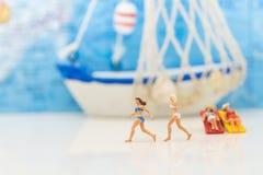 Миниатюрные люди: Купальник женщины нося потеха совместно Корабль предпосылка, использующ как концепция дела перемещения Стоковая Фотография RF