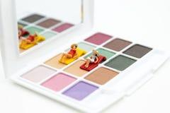 Миниатюрные люди: Ложь женщин на красочных тенях для век Отображайте польза для красоты, косметический продукт стоковые изображения