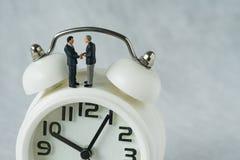 Миниатюрные люди: Малая диаграмма handshaking и стойка бизнесменов стоковое изображение rf