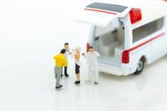 Миниатюрные люди: машина скорой помощи для обработки пациентов далеко от медицинских объектов Польза изображения для концепции зд стоковые фотографии rf
