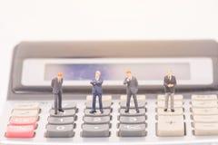 Миниатюрные люди на калькуляторе стоковая фотография rf