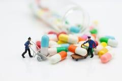 Миниатюрные люди: Помощь работников к moving лекарству Польза изображения для концепции медицинского осмотра стоковое фото
