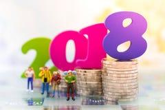 Миниатюрные люди, путешественники группы стоя рядом с с стогом монеток и текст номер красочное деревянное 2018 на верхней части, Стоковые Изображения RF