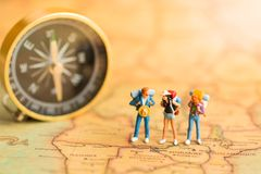 Миниатюрные люди: путешественники стоят на мире карты, идя к назначению Польза как концепция деловых поездок стоковое изображение rf