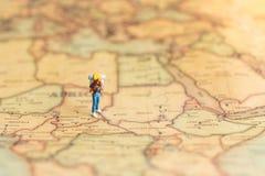 Миниатюрные люди: путешественник идя на карту Использованный для того чтобы путешествовать к назначениям на концепции предпосылки Стоковые Изображения
