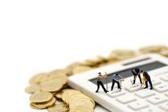 Миниатюрные люди: работник и коробка с монетками и калькулятор  стоковое фото rf