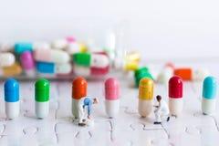 Миниатюрные люди: Работник красит цвет на целебных капсулах Польза изображения для механизмов продукции лекарства стоковое изображение