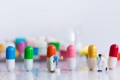 Миниатюрные люди: Работник красит цвет на целебных капсулах Отображайте польза для механизмов продукции лекарства, концепции здра стоковые изображения