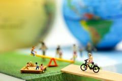 Миниатюрные люди: Семья и дети в парке использующ для концепции стоковая фотография