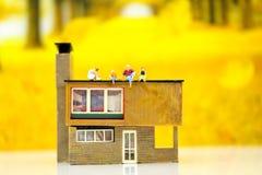 Миниатюрные люди: Сидеть семьи и детей стены с hous стоковое фото rf