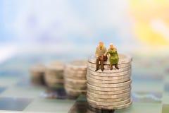Миниатюрные люди, старые пары вычисляют положение na górze монеток стога Польза изображения для планирования выхода на пенсию пре стоковое фото