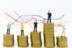 Миниатюрные люди: Стойка бизнесмена группы на стоге монеток, диаграмм дисплея, величин прибыли предпосылки Польза изображения для Стоковое Фото