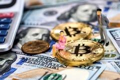 Миниатюрные люди с bitcoins и долларами стоковое изображение