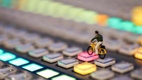 Миниатюрные люди: укомплектуйте личным составом велосипед катания на управлении switcher телефона Стоковые Фотографии RF
