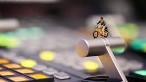 Миниатюрные люди: укомплектуйте личным составом велосипед катания на управлении switcher телефона Стоковые Изображения