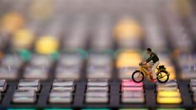 Миниатюрные люди: укомплектуйте личным составом велосипед катания на управлении switcher телефона Стоковые Изображения RF