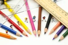 Миниатюрные люди: учитель и студент с красочными чертежными инструментами и неподвижное школьного автобуса, концепции образования стоковая фотография