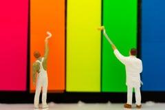Миниатюрные люди: Художники красят красочное части головоломки Польза изображения для искусства, концепции предпосылки Стоковое Изображение