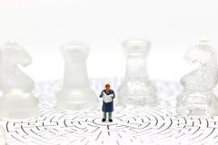 Миниатюрные люди: Чтение бизнесмена на лабиринте с шахмат Концепция Стоковое Фото