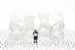 Миниатюрные люди: Чтение бизнесмена на лабиринте с шахмат Стоковая Фотография RF