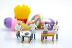Миниатюрные люди: Шеф-повара подготавливают еду для кашевара в кухне Отображайте польза для новых творения меню, еды и концепции  Стоковые Изображения RF