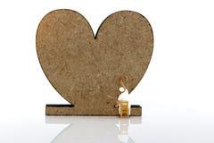 Миниатюрные люди: Щетка работника крася деревянное сердце Искусство шины стоковое изображение