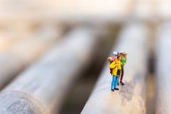 Миниатюрные люди, backpackers идя на камни на реке Концепция каникул приключения образа жизни перемещения Стоковое Изображение RF
