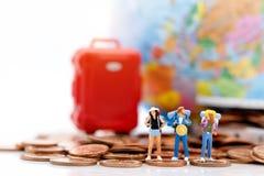 Миниатюрные люди, backpackers стоя на стоге монеток стоковые фотографии rf
