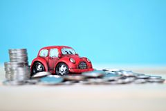 Миниатюрные модель автомобиля и стог монеток на таблице стола Стоковая Фотография