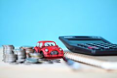Миниатюрные модель автомобиля, стог монеток, калькулятор и бумага тетради на таблице стола офиса Стоковое Изображение RF