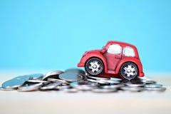 Миниатюрные модель и монетки автомобиля на таблице стола Стоковое фото RF